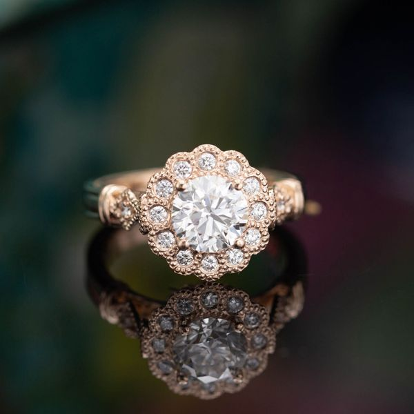 1.01ct round brilliant cut diamond in a scalloped floral diamond halo with milgrain edging. A gorgeous, vintage-inspired design in rose gold..
