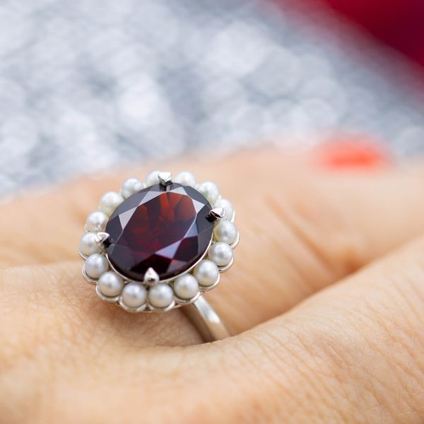 Deep red Mozambique garnet pops against a halo of milky white seed pearls in this vintage inspired ring.