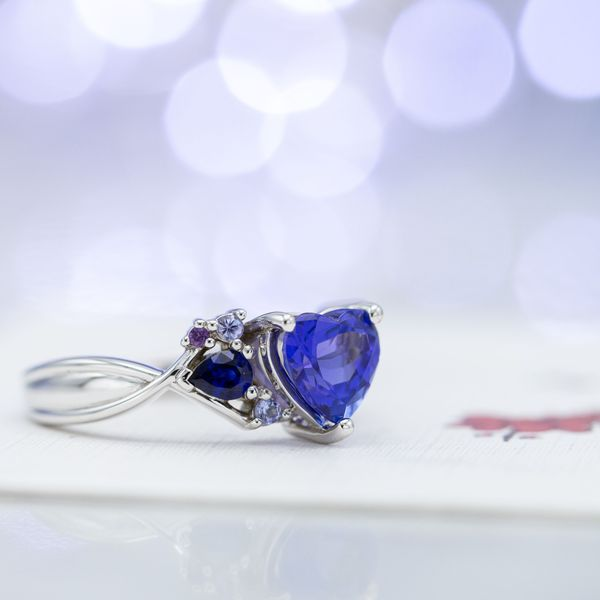 Engagement ring with heart cut tanzanite and asymmetrical clusters of aquamarine, sapphire, and more tanzanite.