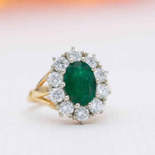 A chunky diamond halo gives this emerald engagement ring a distinctly vintage style.