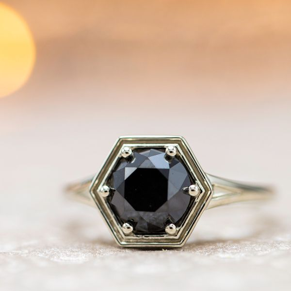 A hexagon basket setting for a round black diamond with a delicate split shank.