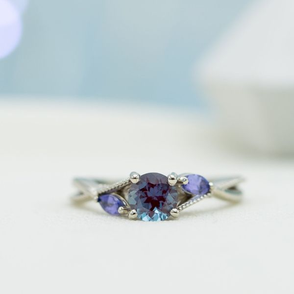 Alexandrite engagement ring with marquise tanzanite side stones in a curving bypass setting.