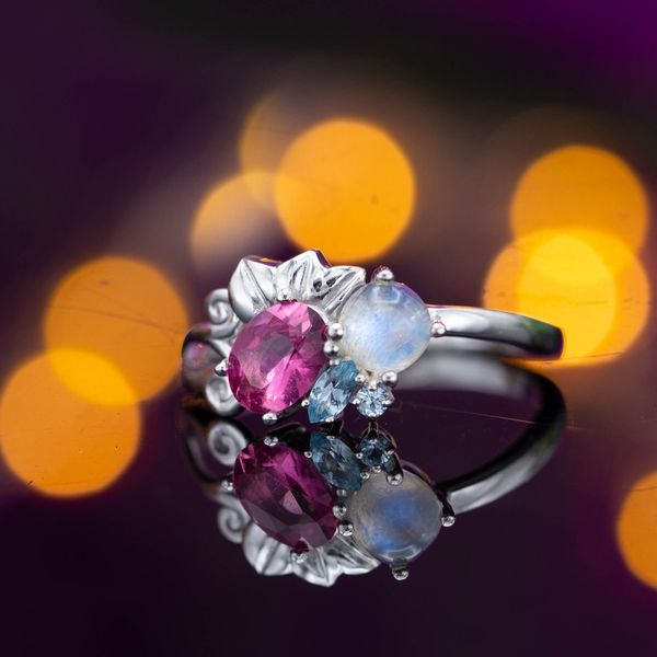 This ring's floral cluster blends color and texture in the pink tourmaline, aquamarine, and moonstone.