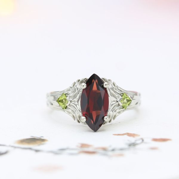 Unique setting with marquise Mozambique garnet framed by wings and peridot accents.