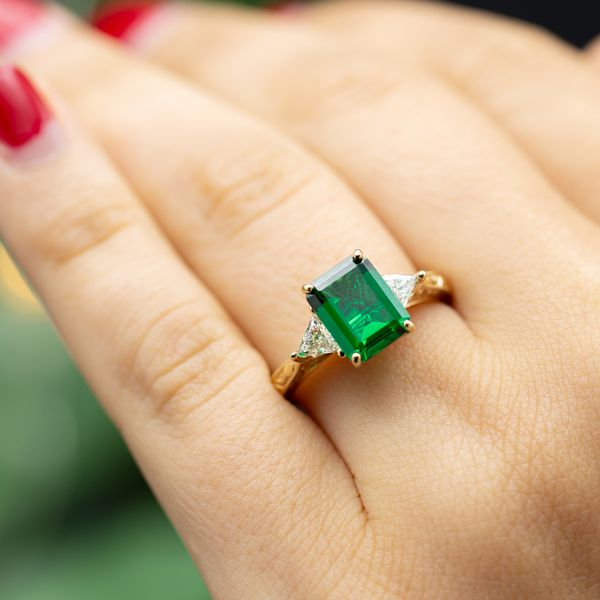 This gorgeous three-stone setting uses trillion cut diamonds to taper from the emerald center stone into the delicate band.
