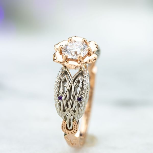 Wonderful details in this bold setting, with open petals framing the center diamond and intricate white gold detailing and amethyst accents on the shoulders.