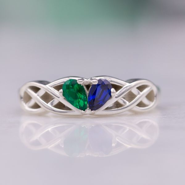 Pear cut emerald and sapphire form a heart-shaped center setting in this Celtic knot ring.