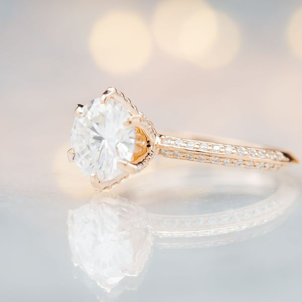 Sleek knife-edge, pave shank with a diamond-studded 6-prong setting for the round brilliant center stone.