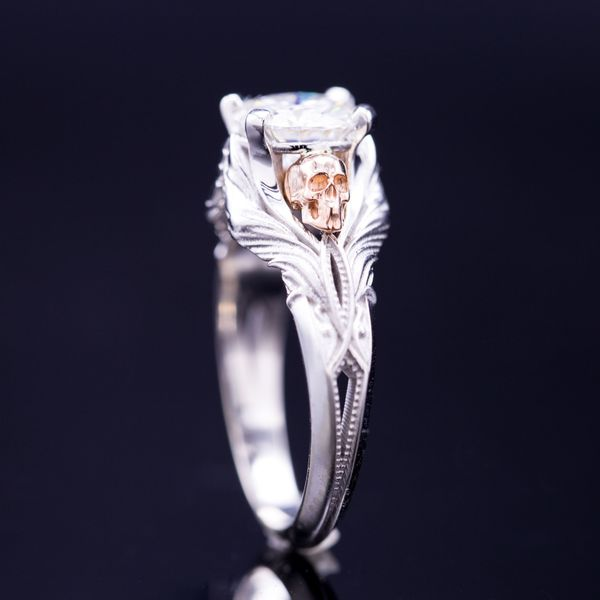 A vintage-inspired diamond ring with rose gold skulls nestled into white gold wings.