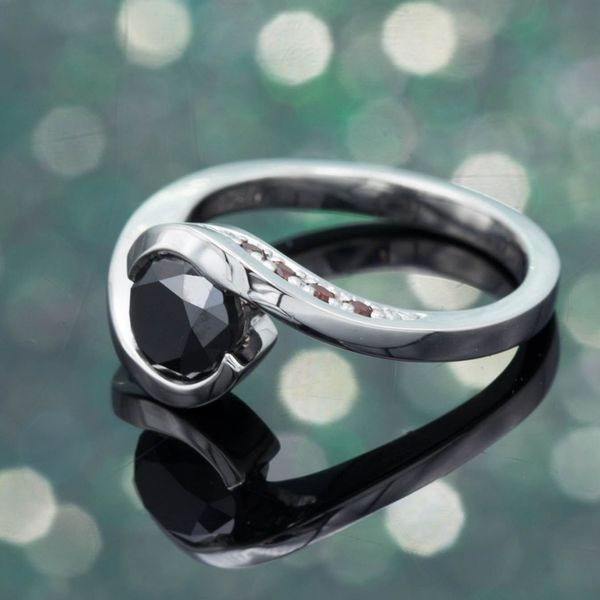 Swooping white gold curves embrace the black diamond in this modern design.