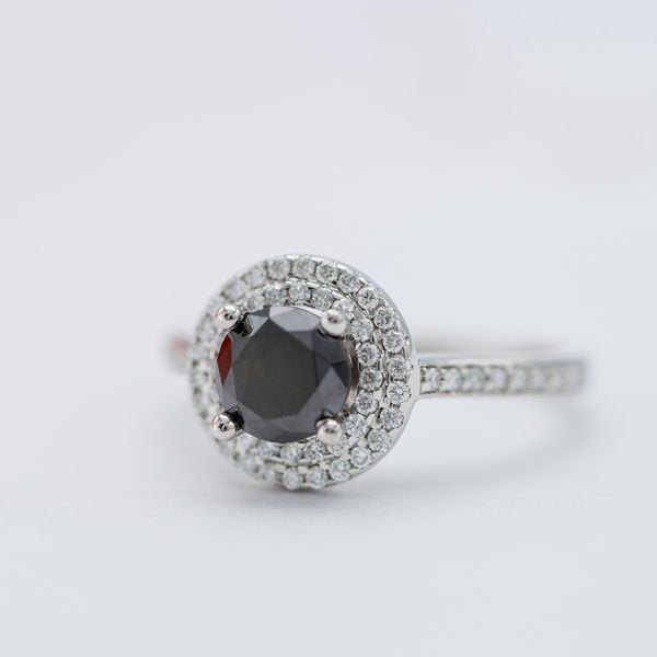 A beautiful double-halo of colorless diamonds adds tons of sparkle and balance to this black diamond engagement ring.