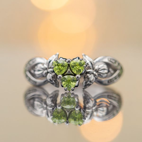 A cluster of trillion-cut peridots creates the center setting in this elegant, floral engagement ring.