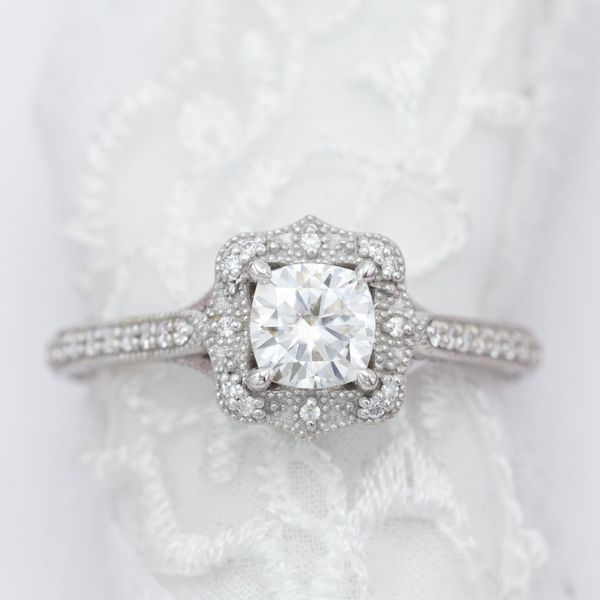 Bead detailing and accent gems decorate the antique frame halo around this cushion cut engagement ring's center stone.