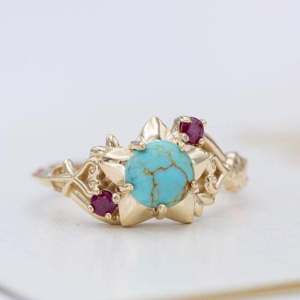 A unique engagement ring with pops of ruby contrasting with the gold-veined turquoise center stone.