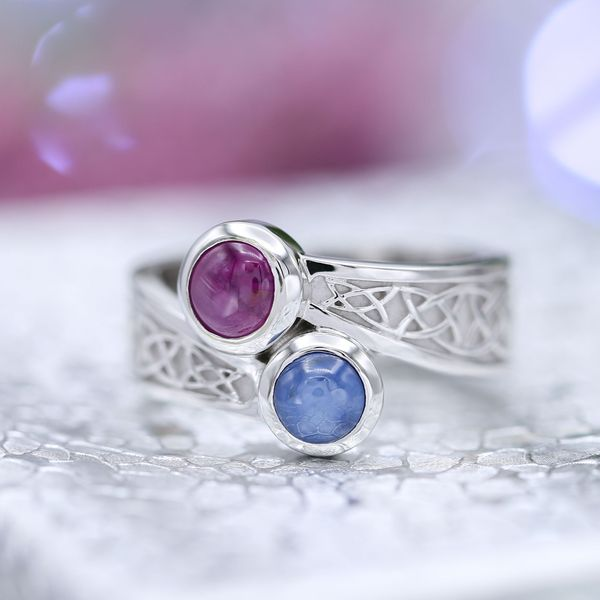 A unique two-stone setting with cabochon cut sapphires and Celtic knot detailing.