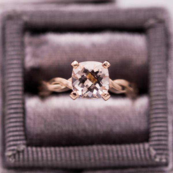 A pretty checkerboard cushion-cut morganite set in an elegant, twisting rose gold shank. We contrasted this delicate ring with a beautifully ornate wedding band.