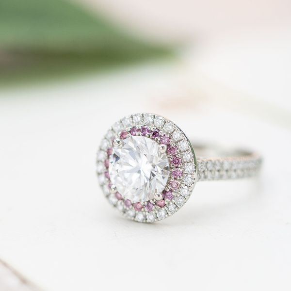 An inner halo of pink diamonds creates subtle contrast between the sparkle of the diamond center stone and the outer diamond halo.