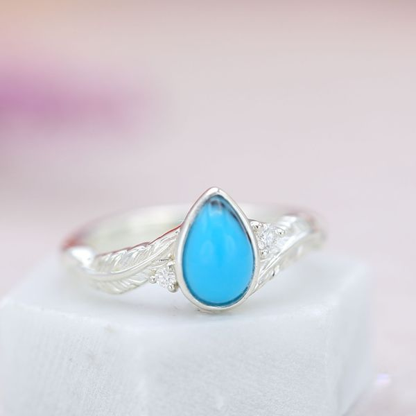 This turquoise has a near-perfect blue with just a single vein to draw the eye. Set in a feather bypass ring.