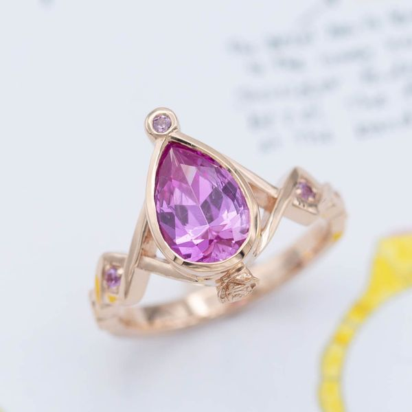 This unique rose gold ring features a vivid, violet-hued pink sapphire in a pear cut.