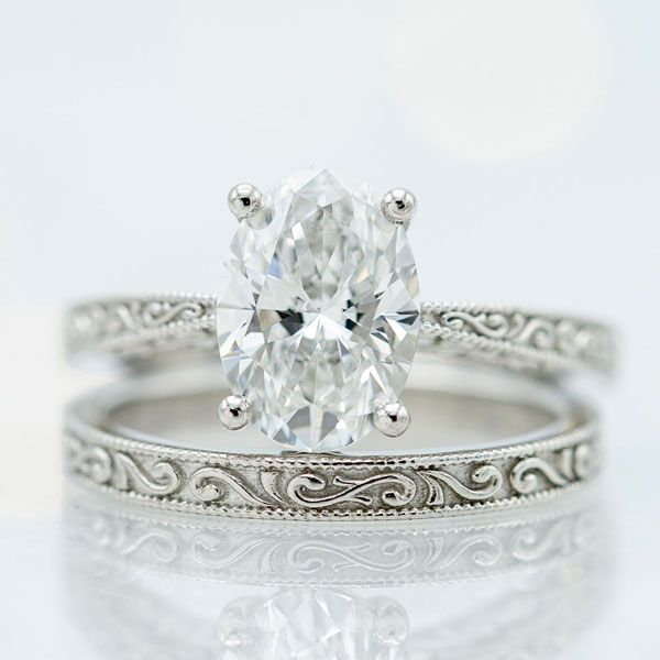 A 1.7ct oval diamond mounted in a platinum setting with intricate vintage detailing inspired by the Huma bird.