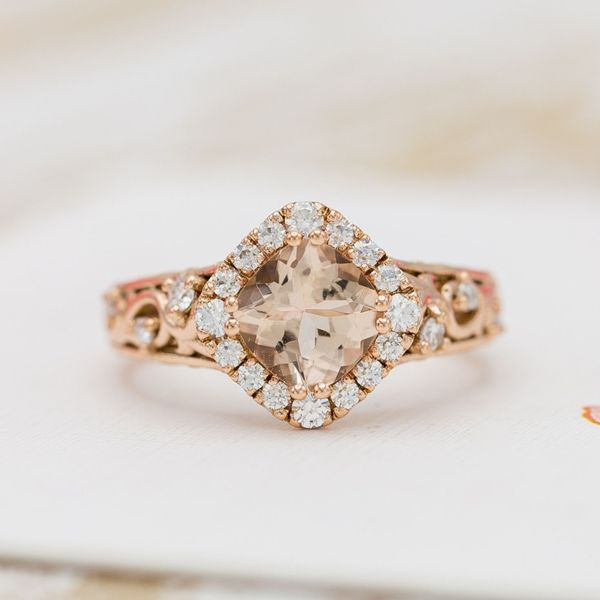 A stunning champagne peach morganite serves as the centerpiece of this rose gold engagement ring.