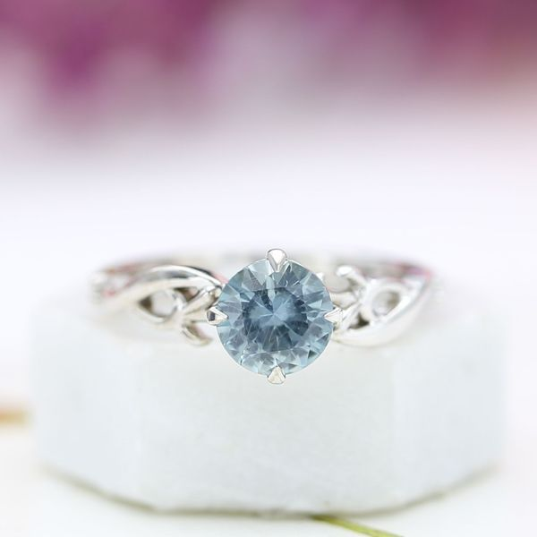 This branching engagement ring shows off a smoky, pale blue Montana sapphire center stone.