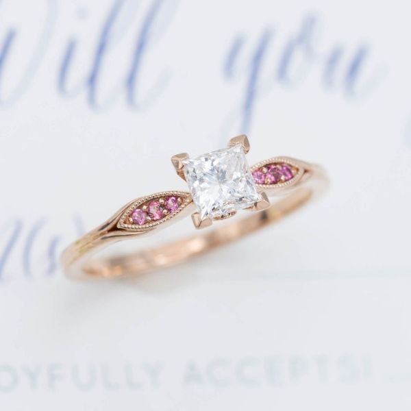 Pink tourmaline provides the perfect pop of accent color to this exquisitely delicate diamond engagement ring.