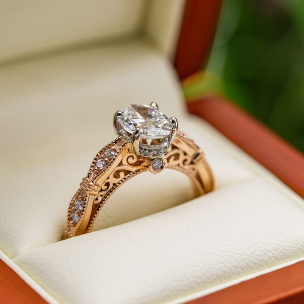 Intricate vintage-inspired details in rose gold surround the 1.2ct oval diamond center stone.
