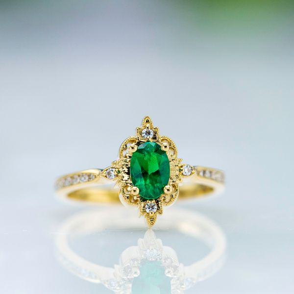 Vintage-inspired emerald engagement ring with an antique halo framing the center stone.