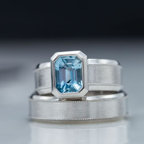 Bold, modern aquamarine engagement ring with a wide band and bezel accenting the gem's geometry.