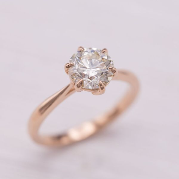 Round diamond solitaire with tapered rose gold shank and 6 prong setting.