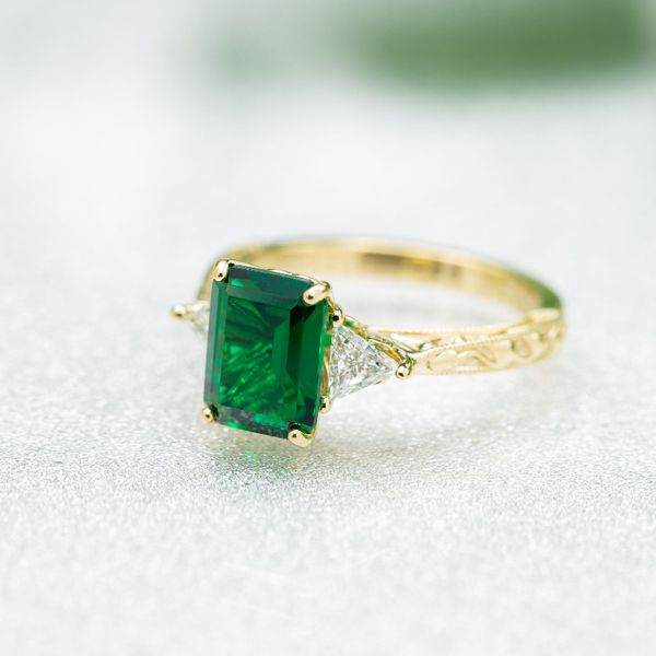 This vintage-inspired 3 stone ring features an emerald cut emerald with trillion cut diamond side stones.