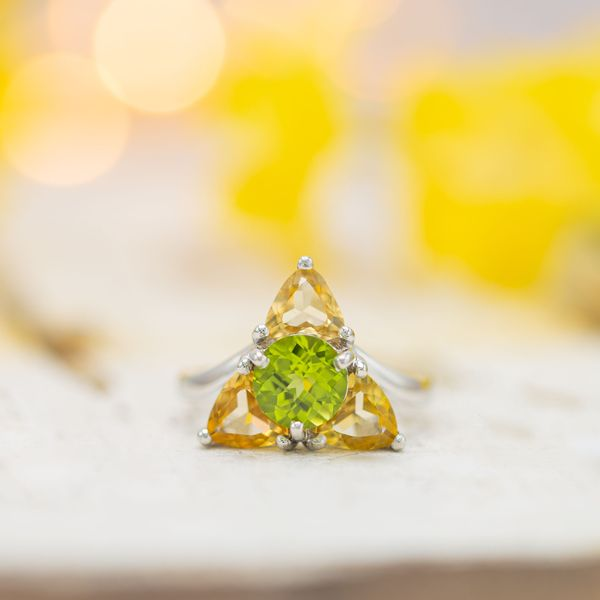 A unique Triforce-inspired engagement ring with precious topaz and peridot creating the Zelda-inspired triangular setting.