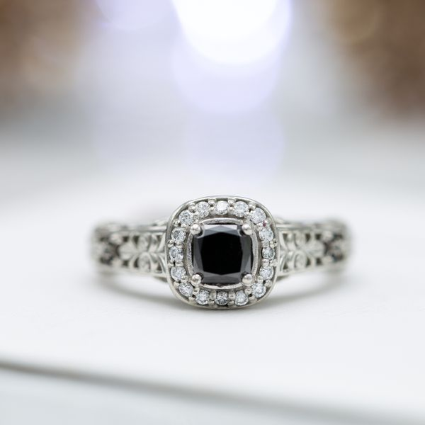 Cushion cut black diamond halo ring with an open scroll design on the shank.