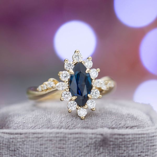 Midnight blue marquise sapphire surrounded by a sunburst halo and curvy, tapered band.