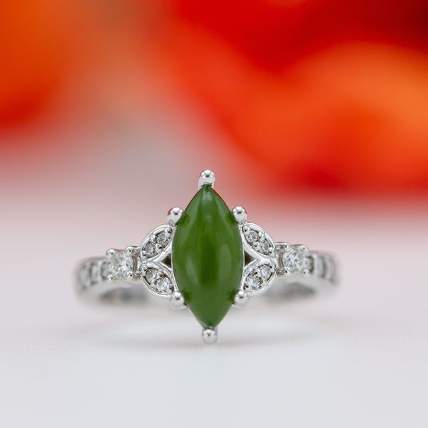 This jade engagement ring echoes the marquise shape of the center stone with the diamond-studded split band around it.