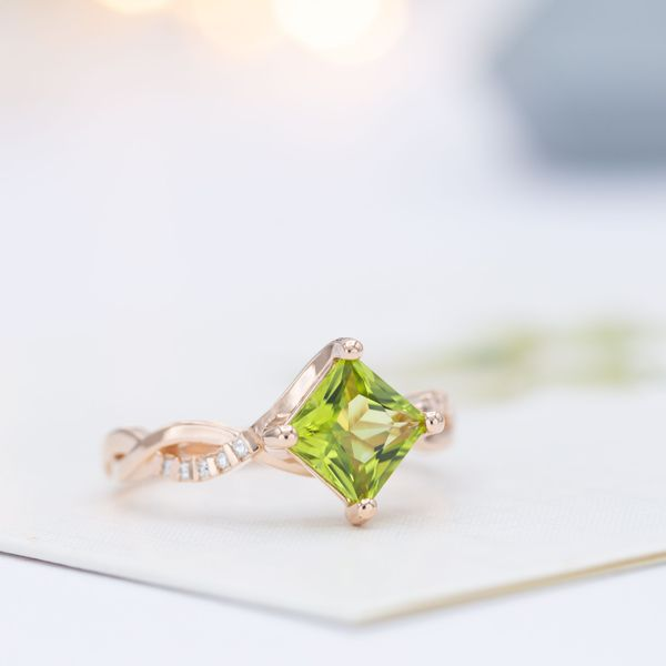 Bypass engagement ring in rose gold with a kite set princess cut peridot center stone.