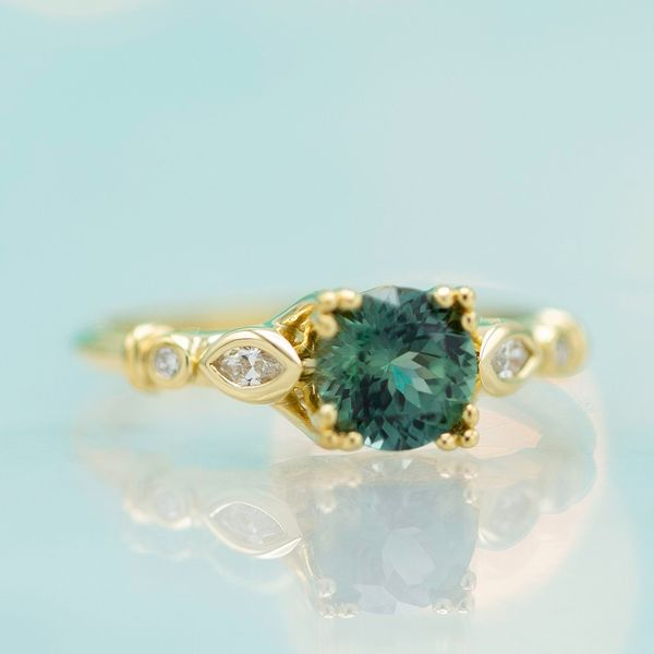 Bluish-green sapphire engagement ring with a gold, triple prong setting.