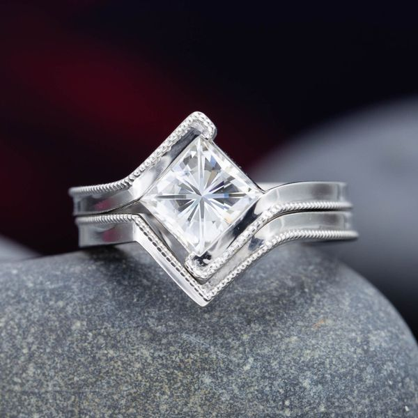 A princess cut center stone is set at an angle, its lines reinforced by the similarly angular bypass shank and matching wedding band.