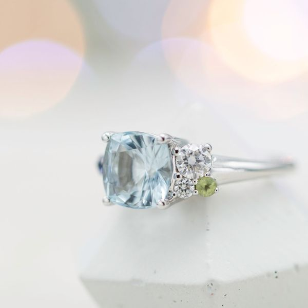 Modern aquamarine engagement ring with asymmetrical side clusters of diamonds, peridot and blue sapphire.