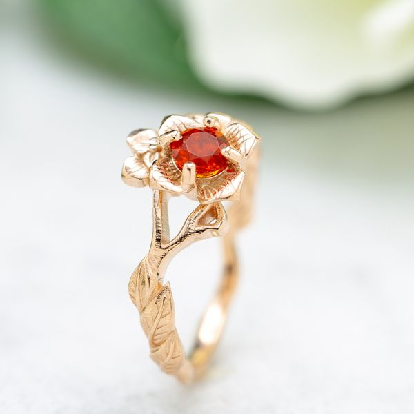 Inspired by the persimmon, the blossom in this rose gold ring features a cherry fire opal.
