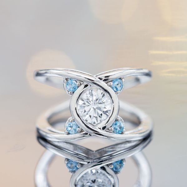 Unique diamond and topaz engagement ring inspired by Bernoulli's lemniscate, an infinity-like symbol wrapped around the finger.