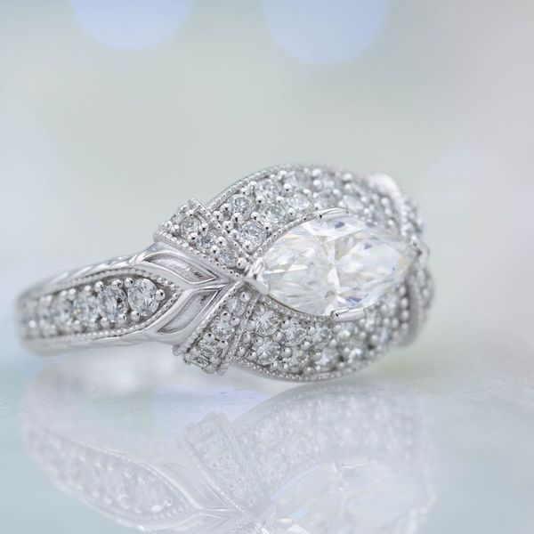 East-west set marquise diamond with a dense setting of round accent diamonds in varying sizes.