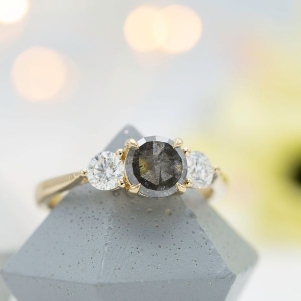 The dark gray tone of this salt & pepper diamond's body creates a perfect contrast with white diamonds in a three stone setting.