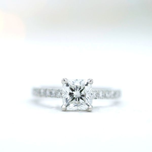 A clean, timeless cushion cut diamond solitaire engagement ring.