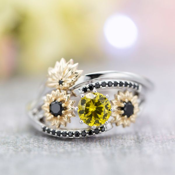 This yellow sapphire engagement ring uses mixed gold colors and black spinel to create a beautiful sunflower cluster.