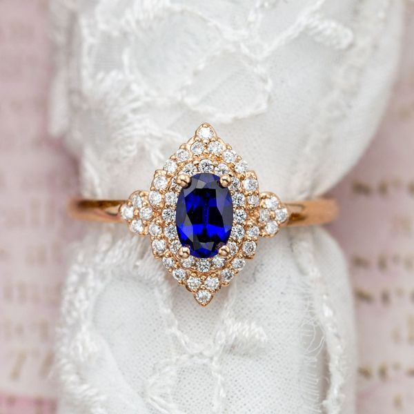 A vintage-inspired blue sapphire engagement ring with a stylized double-halo of diamonds around the lab-created center stone.