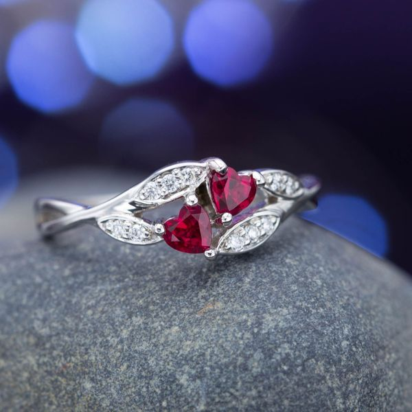 Two-stone setting with heart cut rubies and bypass-style diamond-accented shank.