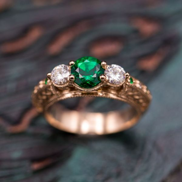 This vintage-inspired ring features a three-stone setting of emerald and moissanite. The intricate detailing is inspired by Celtic rope.