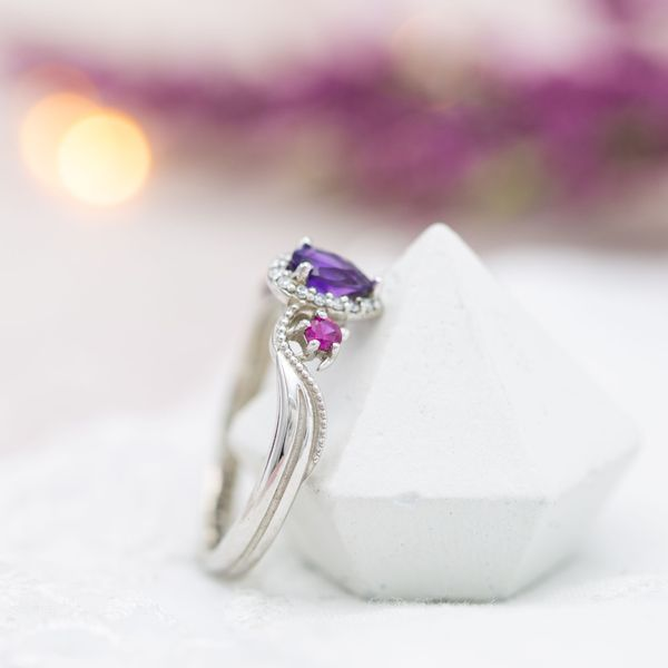 The dainty turtle side settings sit in the wave-inspired curve of the ring's shank.
